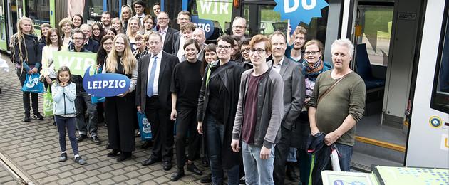 """Menschen stehen vor einer weiß-blau-grün beklebten Straßenbahn mit dem Schriftzug """"Jahr der Demokratie"""""""