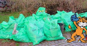"""Viele volle grüne Müllsäcke mit der Aufschrift """"Stadt Leipzig"""" liegen auf einem Haufen im Freien. Daneben ist ein kleiner Löwe eingezeichnet, der einen Putzeimer und einen Lappen in den Händen hält."""