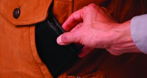 Eine Hand greift in eine Tasche und zieht eine Geldbörse heraus.