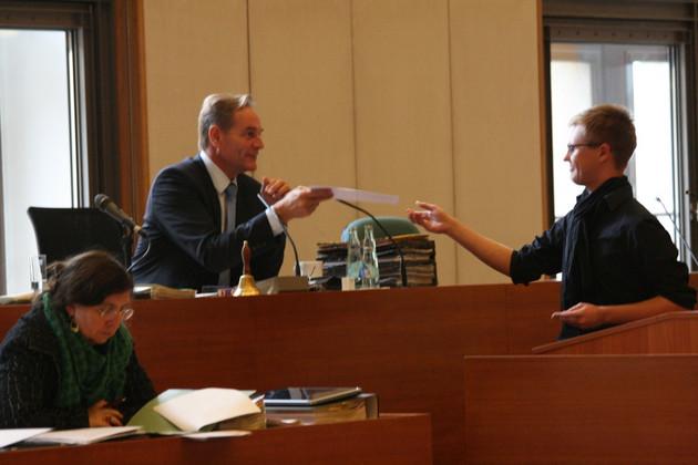 Ein junger Mann in schwarzem Hemd und mit schwarzem Schal übergibt dem sitzenden Oberbürgermeister Burkhard Jung ein Schriftstück