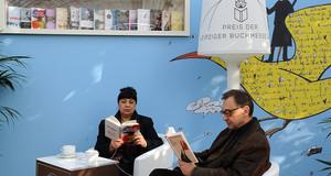 Zwei Leser blättern durch die Bücher der Preisträger