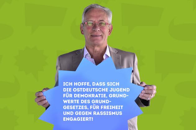 """Ein Mann hält ein Schild mit dem Statement """"Ich hoffe, dass sich die Ostdeutsche Jugend für Demokratie, Grundwerte des Grundgesetztes, für Freiheit und gegen Rassismus engagiert!""""."""