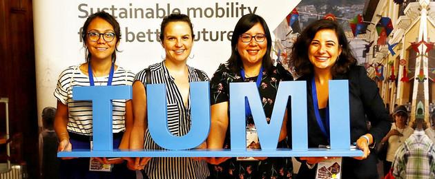 """Vier Frauen halten einen großen Blauen Schriftzug """"TUMI"""" hoch und lächeln in die Kamera."""
