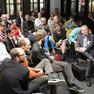 ca. 40 Menschen sitzen in einem Raum und diskutieren