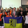 Gruppenfoto mit Leipzigs Oberbürgermeister Burkhard Jung und einer chinesischen Schulklasse, die Gruppe hält gemeinsam eine Leipzig-Fahne