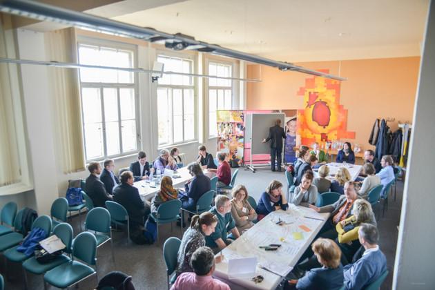 Blick von oben in einen offenen Raum. Darin sitzen zahlreiche Menschen um verschiedene Tische herum, diskutierend, schreibend, lächelnd.