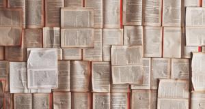 Viele aufgeschlagene Bücher, die nebeneinander auf einer Fläche liegen
