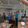 Viele ältere Menschen in einem mit Luftschlangen und Ballons geschmückten Raum. Sie tragen Partyhüte, einige tanzen.