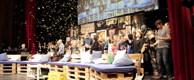 Die Bühne der Preisverleihung der Visionale 2015 im Schauspiel Leipzig. Auf der Bühne stehen viele Menschen unter einer Videoleinwand. Im Vordergrund stehen aus Europaletten gebaute Sofas mit Kissen. Es regnet Konfetti.