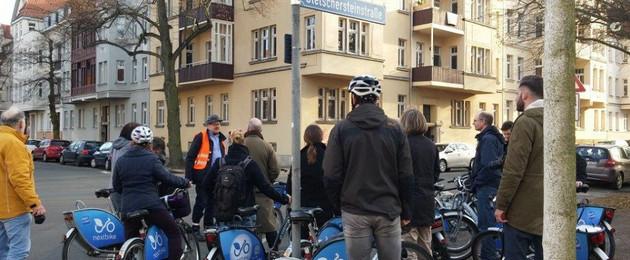 Mehrere Fahrradfahrer stehen am Straßenrand und hören einem Mann in Warnweste zu.