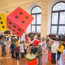 In der rechten Bildhälfte sieht man große gelbe und rote Würfel als Dekoelement. An mehreren Stehtischen probieren Kinder und Erwachsene verschiedene Brettspiele aus.