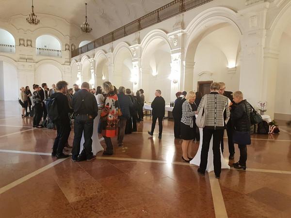 Verschiedene Personen stehen an Stehtischen in der Oberen Wandelhalle des Neuen  Rathauses.