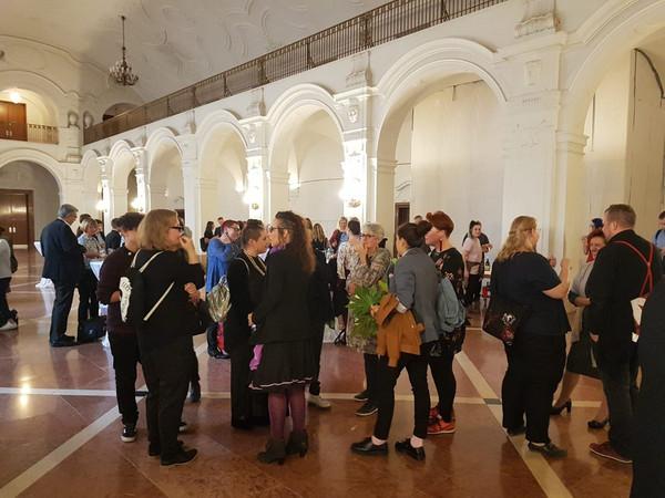 Einige Personen stehen an Stehtischen in der Oberen Wandelhalle des Neuen Rathauses und unterhalten sich.