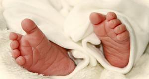 Babyfüße in weißer Decke