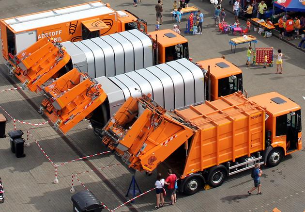 Mehrer Müllfahrzeuge aus der Luft gesehen. Daneben verschiedene Infostände und Besucher.