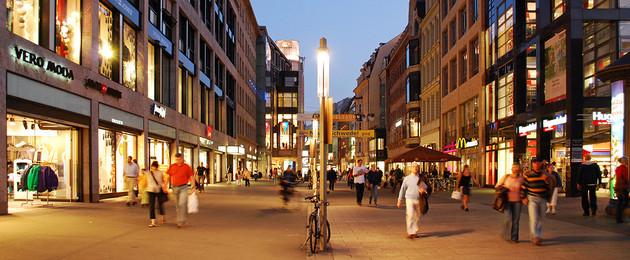 Leipziger Einkaufsstraße Petersstraße mit beleuchteten Geschäften und Einkaufenden.