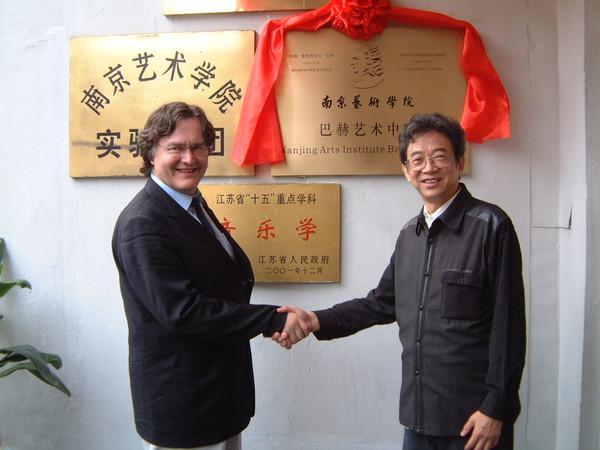 Prof. Biller, ehemaliger Thomaskantor, und der damalige Leiter des Nanjing Arts Institute schütteln sich die Hände, im Hintergrund goldene Plakette mit rotem Band als Eingangstafel zum Bach-Zentrum