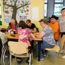 Auf diesem Bild sitzt eine Gruppe im inklusiven Nachbarschaftszentrum des Vereins Mobiler Behindertendienst Leipzig beisammen.