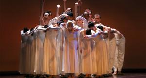 Mehrere Tänzer in weißen fließenden Gewänder formieren sich zu einem Kreis