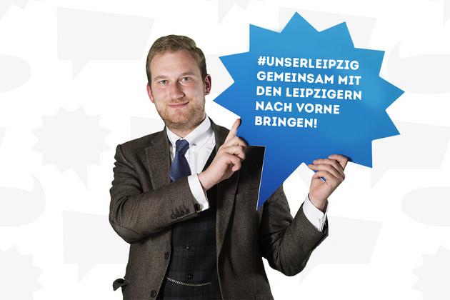 """Ein Mann hält ein Schild mit dem Statement """"#unserleipzig– Gemeinsam mit den Leipzigern nach vorne bringen!""""."""