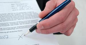 Ein Mann hält einen Stift auf eine Blatt Papier mit einem Vertragstext. Dort ist eine Stelle zum Unterschreiben markiert.