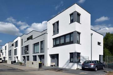 Bild wird vergrößert: Eine Reihe von modernen Stadthäusern mit weißer und grauer Fassade.