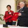 Frau Xu und Prof. Häuser halten gemeinsam ein rotes Mäppchen mit dem unterzeichneten Kooperationsvertrag in den Händen.