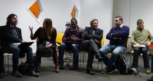 Diskussionsrunde mit verschiedenen Menschen, die auf Stühlen sitzen