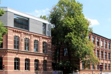Bild wird vergrößert: Ein historisches zweigeschossiges Kontorhaus aus roten Ziegeln wurde um einen modernen grauen Aufsatz mit großem Fenster ergänzt.