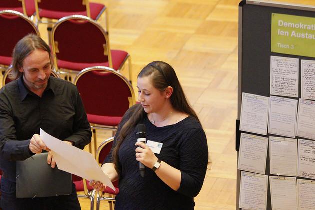 Frau Heller steht mit Mikrofon in der Hand und redet. Neben ihr ist eine Pinnwand mit angehefteten Zetteln.