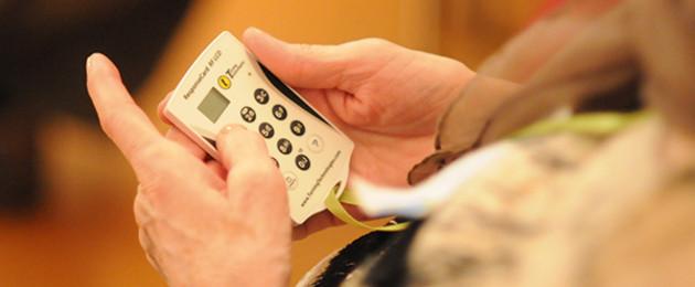 Alte Hände halten ein elektronisches Abstimmungsgerät