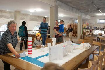 Bild wird vergrößert: Kinder und Erwachsene stehen vor einer aus Papier und anderem Material gestalteten Stadt, die auf einem großen Holztisch steht.