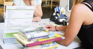 Nahaufnahme zweier Frauen, die sich mit den Armen auf einem Tisch abstützen. Die eine zeigt der anderen etwas in einem Flyer. Auf dem Tisch liegen Bücher und Büromaterialien.