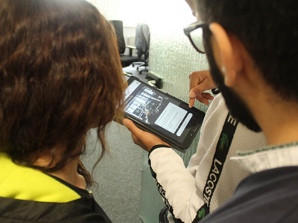 Zwei Menschen schauen auf ein Tablet.