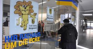 En Bürger betritt durch die Glastür das Bürgeramt in der Wiedebach-Passage  in Leipzig Connewitz