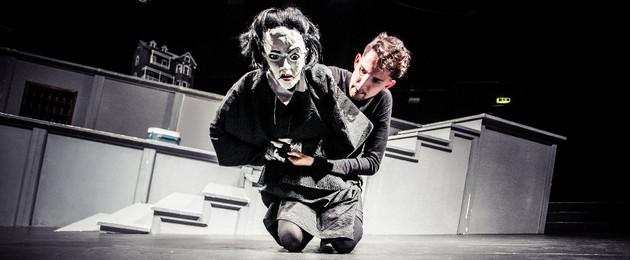 Ein Mann kniet auf der Bühne und hält eine große Puppe mit weißem Gesicht, schwarzen Haaren, roten Lippen und einem schwarzen Umhang in den Händen. Im Hintergrund eine Treppe.