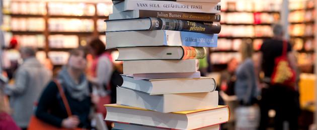 Ein Bücherstapel, im Hintergrund Messeregale und Besucher