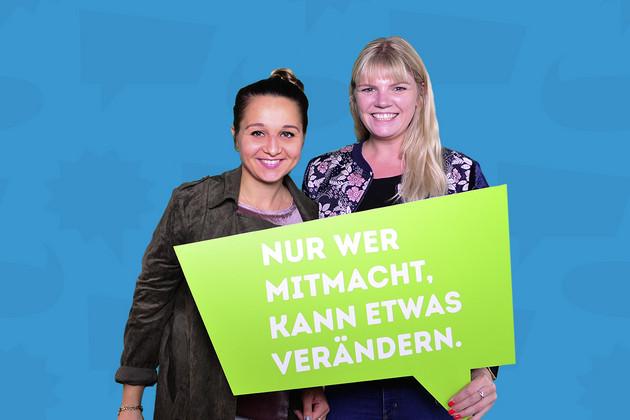 """Zwei Frauen halten eine Schild mit dem Statement """"Nur wer mitmacht, kann etwas verändern.""""."""