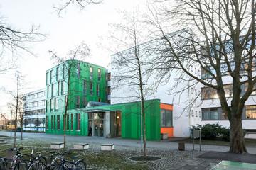 Bild wird vergrößert: Gebäude der Franz Mehring Schule. Auffälliger grüner Eingangsbereich und mehrstöckiges Gebäude mit vielen Fensterflächen.