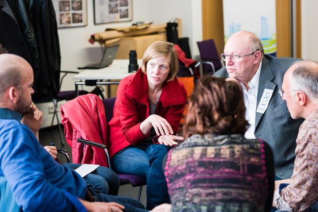 Kleine Arbeitsgruppe im Sitzkreis, vorne eine Frau im roten Pullover