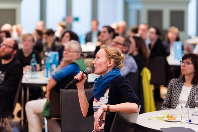 Eine Frau sitzt im Publikum und hat das Mikro in der Hand.