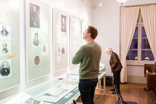 Ein Mann und eine ältere Frau betrachten interessiert die Ausstellungstafeln und -vitrinen im Museum des Schumann-Hauses