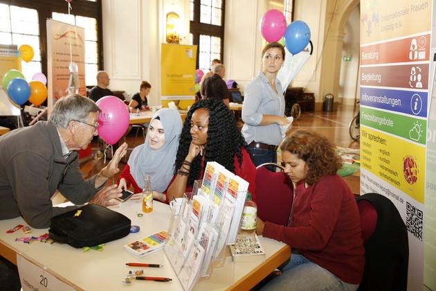 Drei Frauen lassen sich am Stand des Vereins Internationale Frauen beraten.
