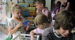 Kinder greifen in eine Kiste mit Spielzeug