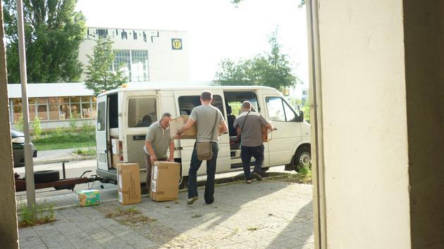 In einen weißen VW-Transporter laden drei Männer braune Umzugskartons mit Hilfsgütern ein