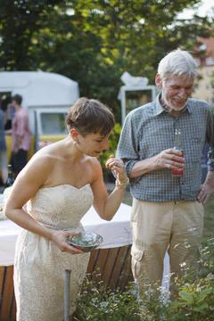 Bild wird vergrößert: Eine Frau und ein Mann stehen in einem Garten und schauen auf Blumen in einem Beet.