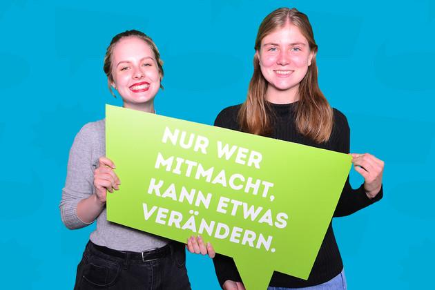 Zwei Frauen zur Statementkampagne zum Jahr der Demokratie mit grüner Sprechblase auf der steht: Nur wer mitmacht, kann etwas verändern.