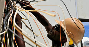Ein Mann mit Helm und vielen Elektrokabeln beim Arbeiten.