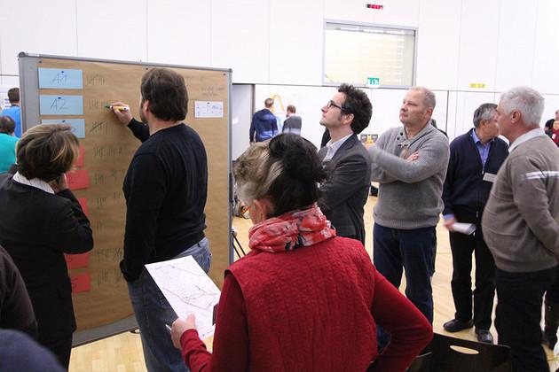 Teilnehmer eines Workshop schauen und schreiben an eine Tafel. Thema ist die Straßenbahnerweiterung in Probstheida.