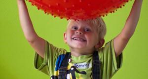 Ein frech dreinschauendes Kind, einen Spielball über dem Kopf haltend